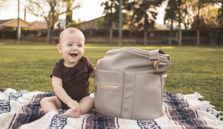 smiling-baby-sitting-next-to-a-big-baby-bag-at-a-park_t20_QQy9gG