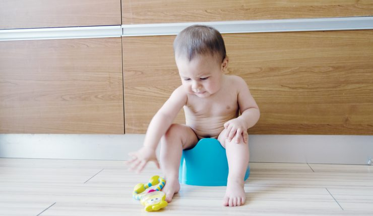 cute six months old baby boy siting on the blue potty early development concept